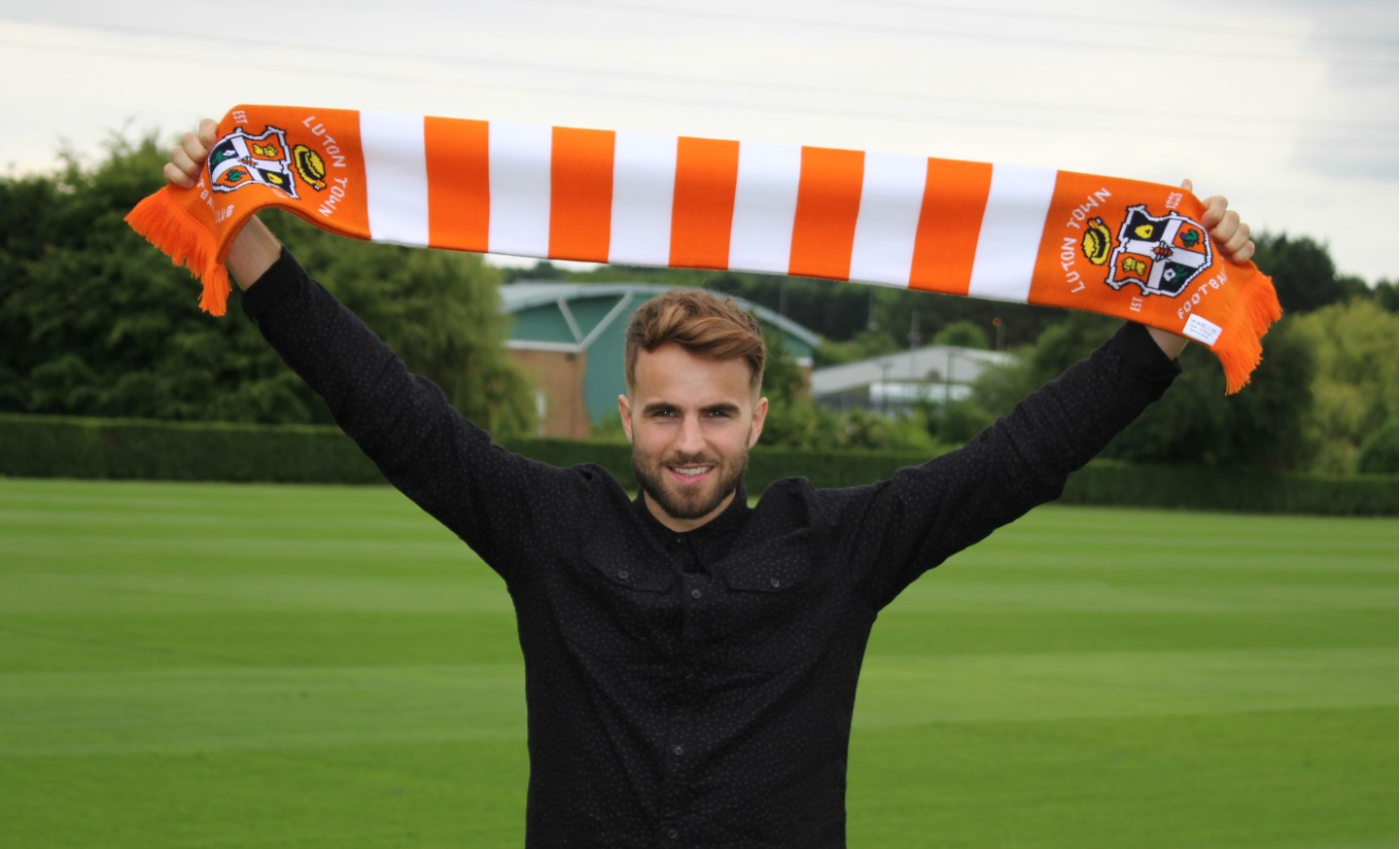 Andrew Shinnie holds a Hatters scarf aloft at The Brache training ground
