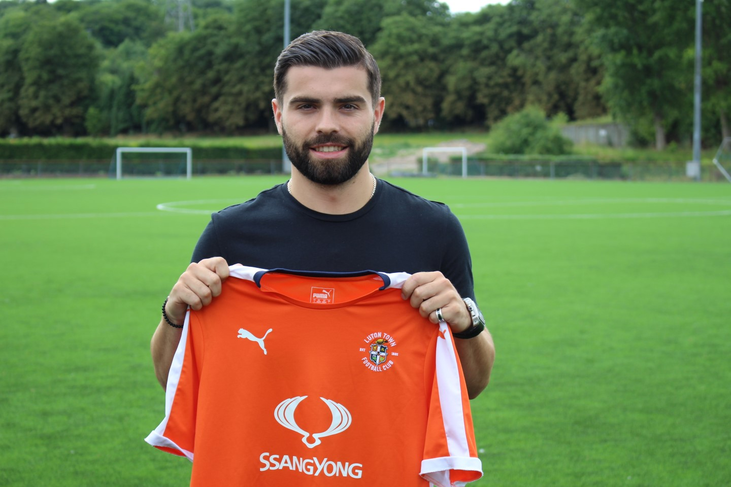 Elliot Lee holds the Luton Town shirt at the training ground after his return to the club