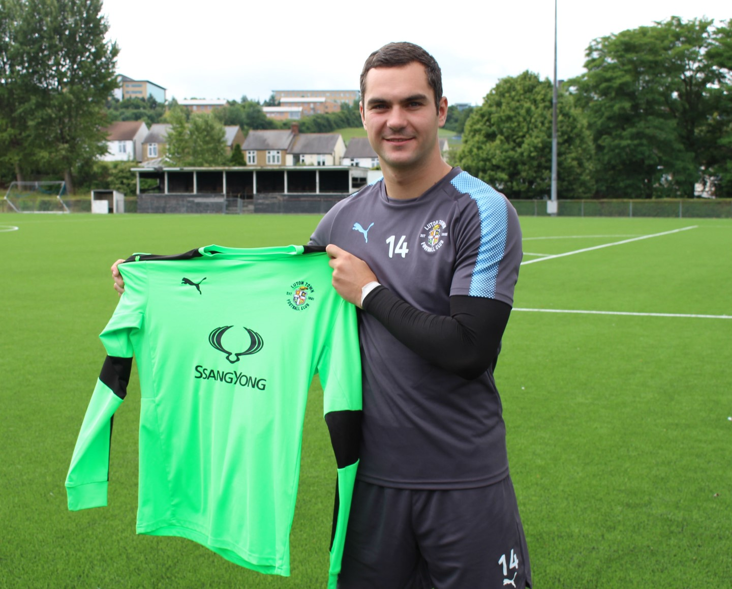 New signing James Shea holds the Town keeper's shirt up at The Brache