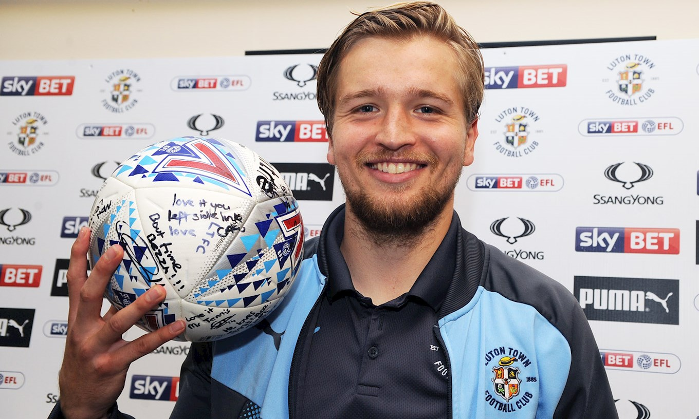 Luke Berry holds the matchball signed by all of his team-mates following his hat-trick against Stevenage in October 2017