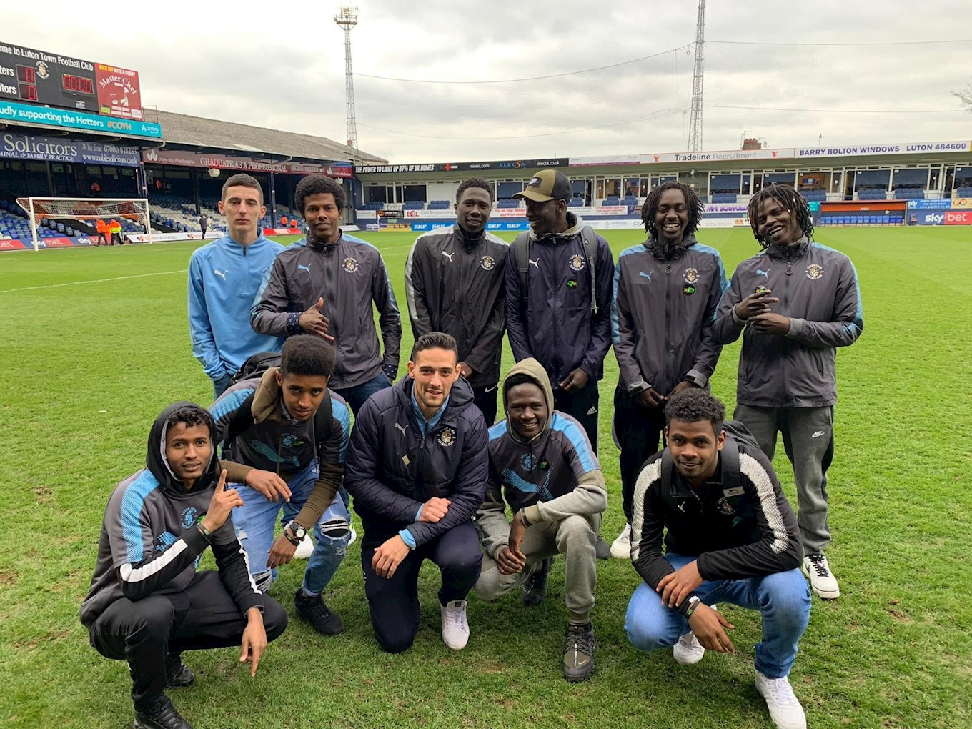 The group of young male asylum seekers from Sudan on the Kenilworth Road pitch ahead of the Blackpool game