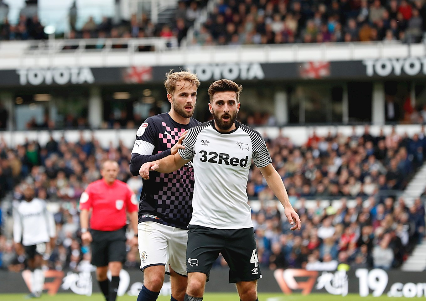 Hatters playmaker Andrew Shinnie gets tight to his brother Graeme, the Derby County midfielder, in the game at Pride Park