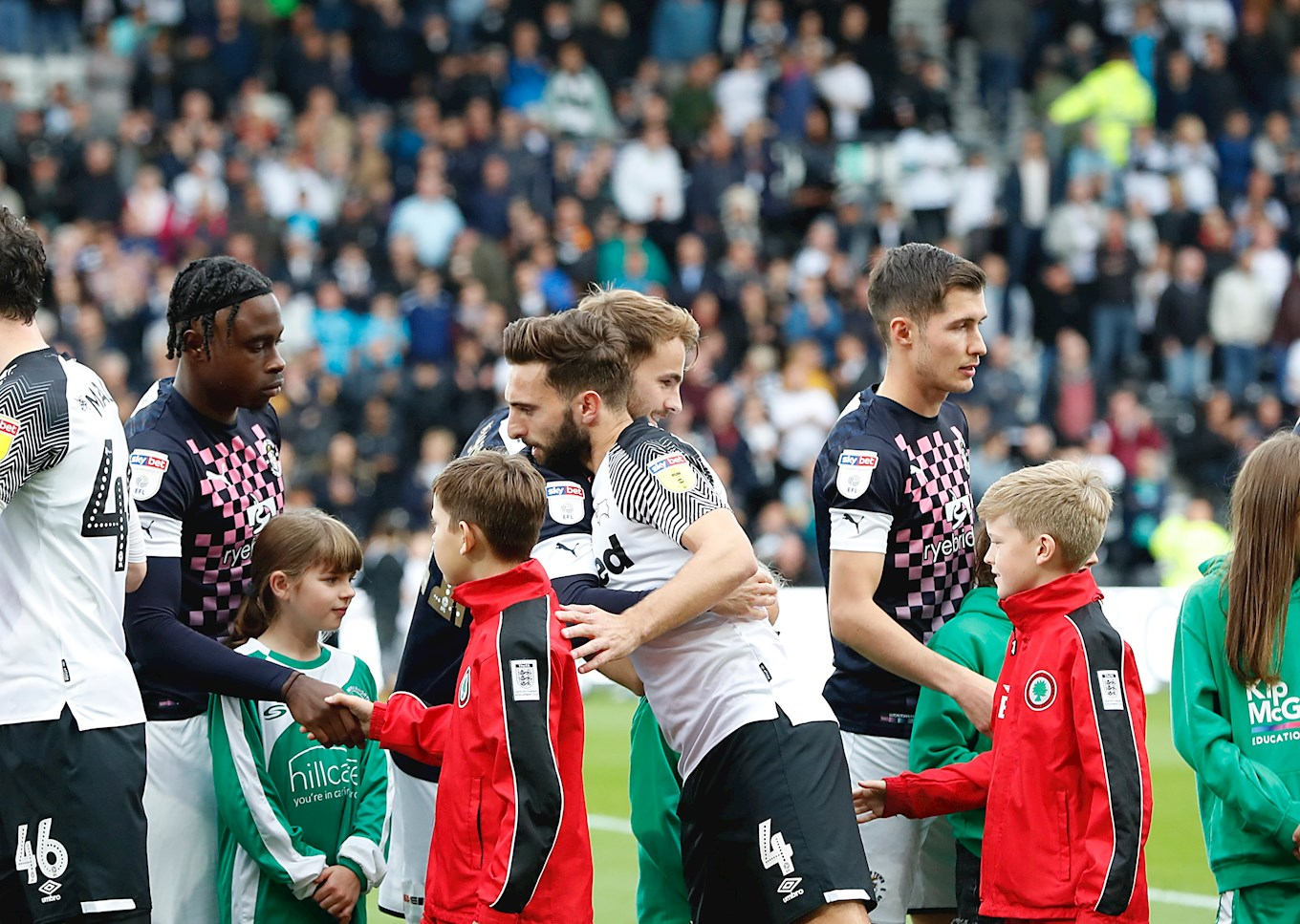 The Shinnie brothers embrace during the pre-match handshakes at Pride Park