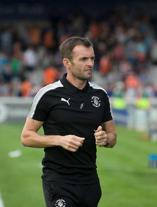 Hatters boss Nathan Jones wears the Prostate Cancer UK 'Man of Men' badge during the recent game at Lincoln