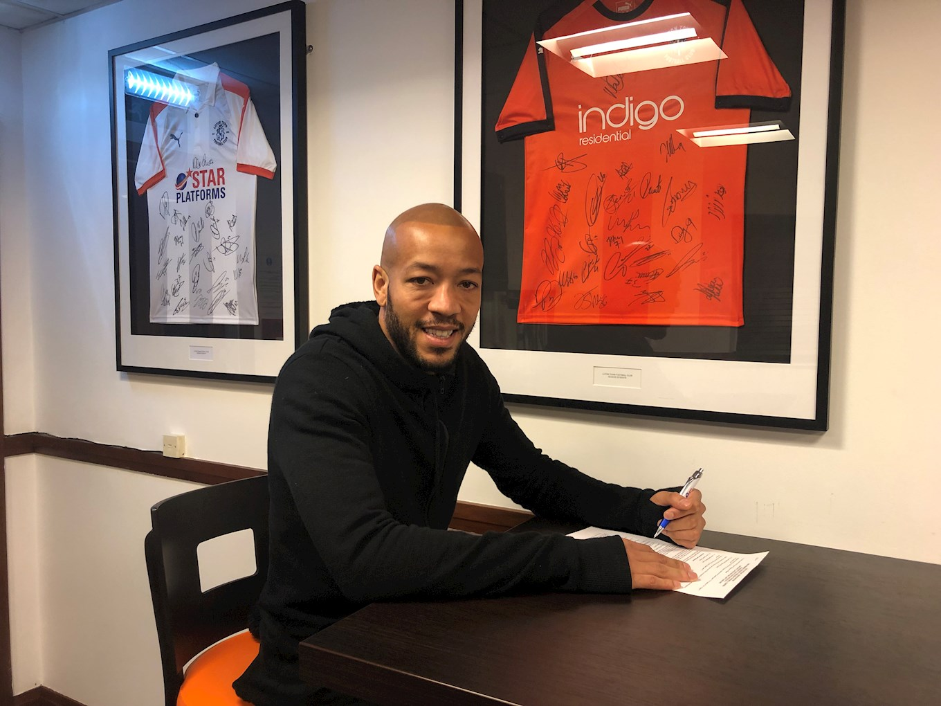 Alex Baptiste signs his loan forms at Kenilworth Road