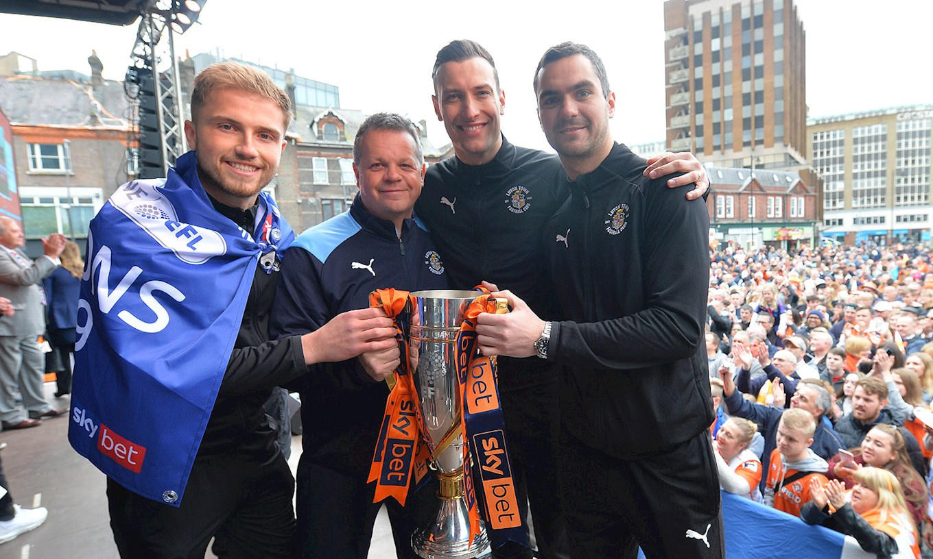 Harry celebrates League One promotion with goalie coach Kevin Dearden and fellow keepers Marek Stech and James Shea on stage in St George's Square in May